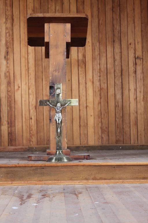 A crucifix and some wooden pews are the only furnishings